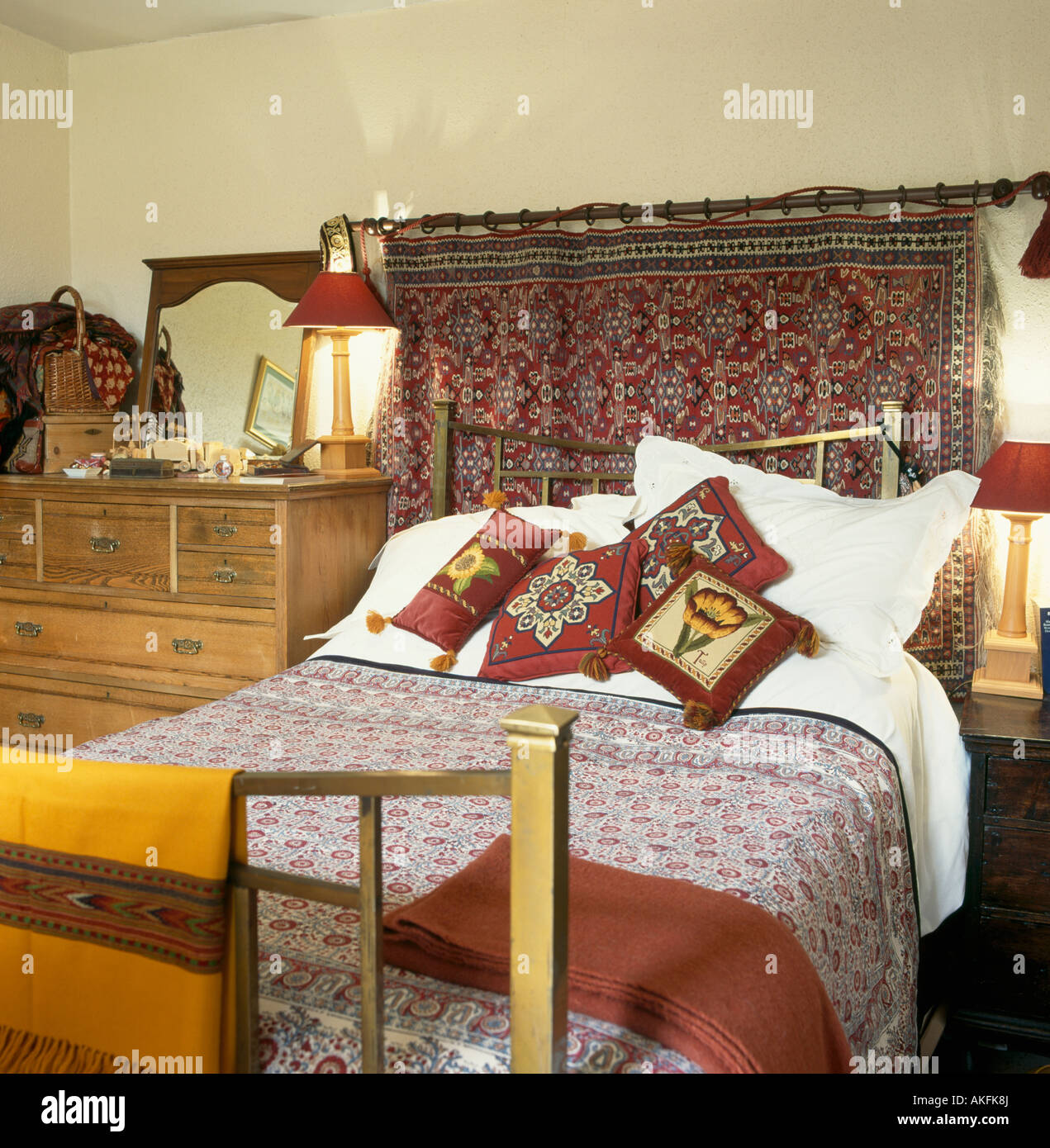 Indian Wall Hanging Above Brass Bed With Patterned Red Cushions And  Bedcover In Small Bedroom