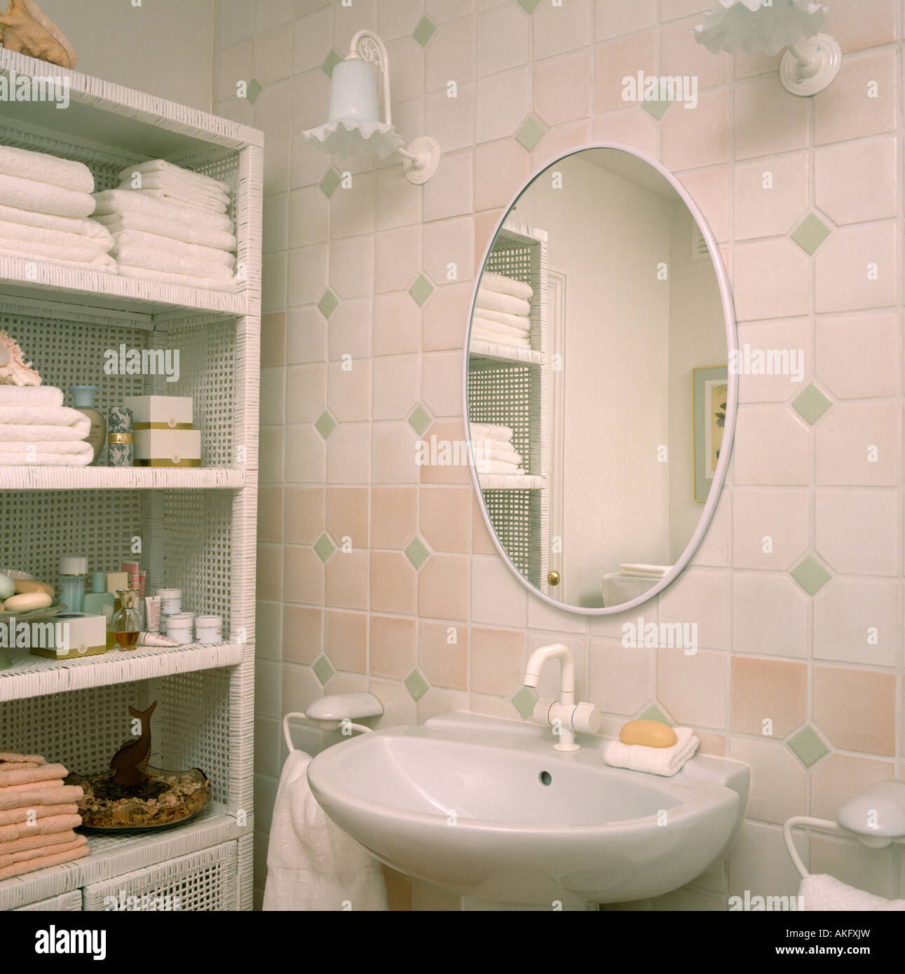 Oval Mirror On Pink And White Tiled Wall Above Basin In Small Bathroom With  Towels And