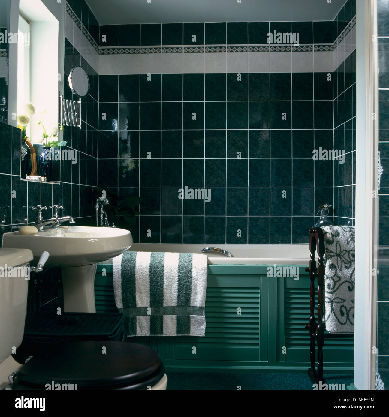 Green Striped Towel On White Bath With Green Panelling In Bathroom Stock Photo, Royalty Free