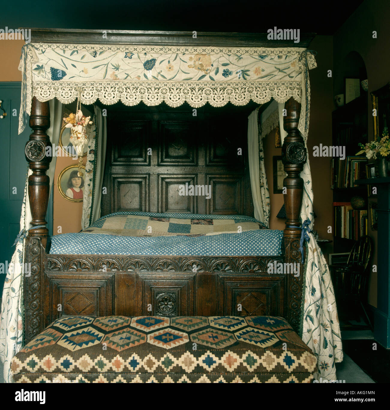 Floral patterned canopy on antique carved wooden bed in country bedroom with kelim upholstered ottoman & Floral patterned canopy on antique carved wooden bed in country ...