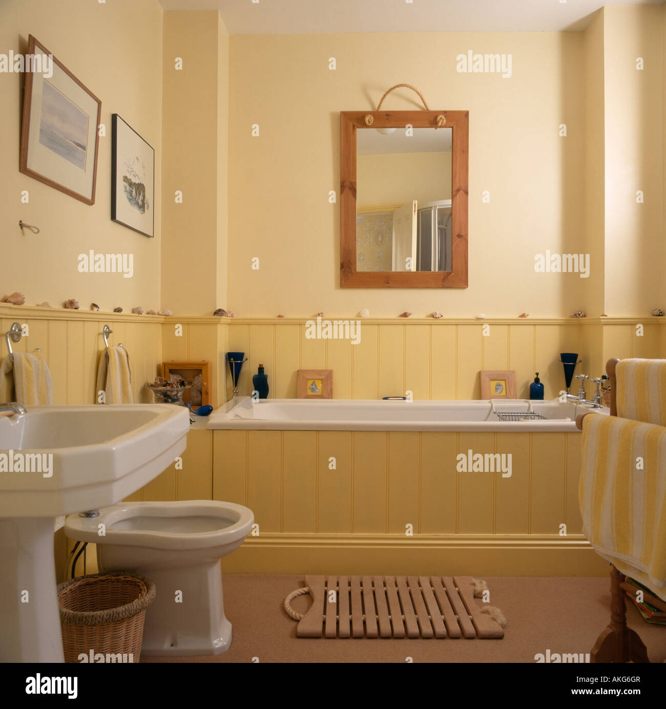 wooden mirror above dado panelling and panelled bath in
