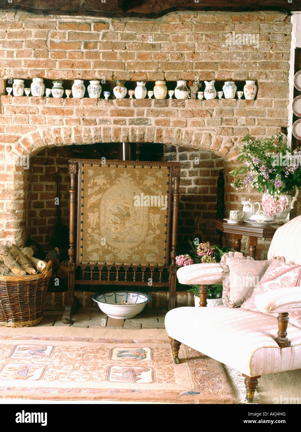 Collection of china in narrow alcove on brick wall above fireplace ...