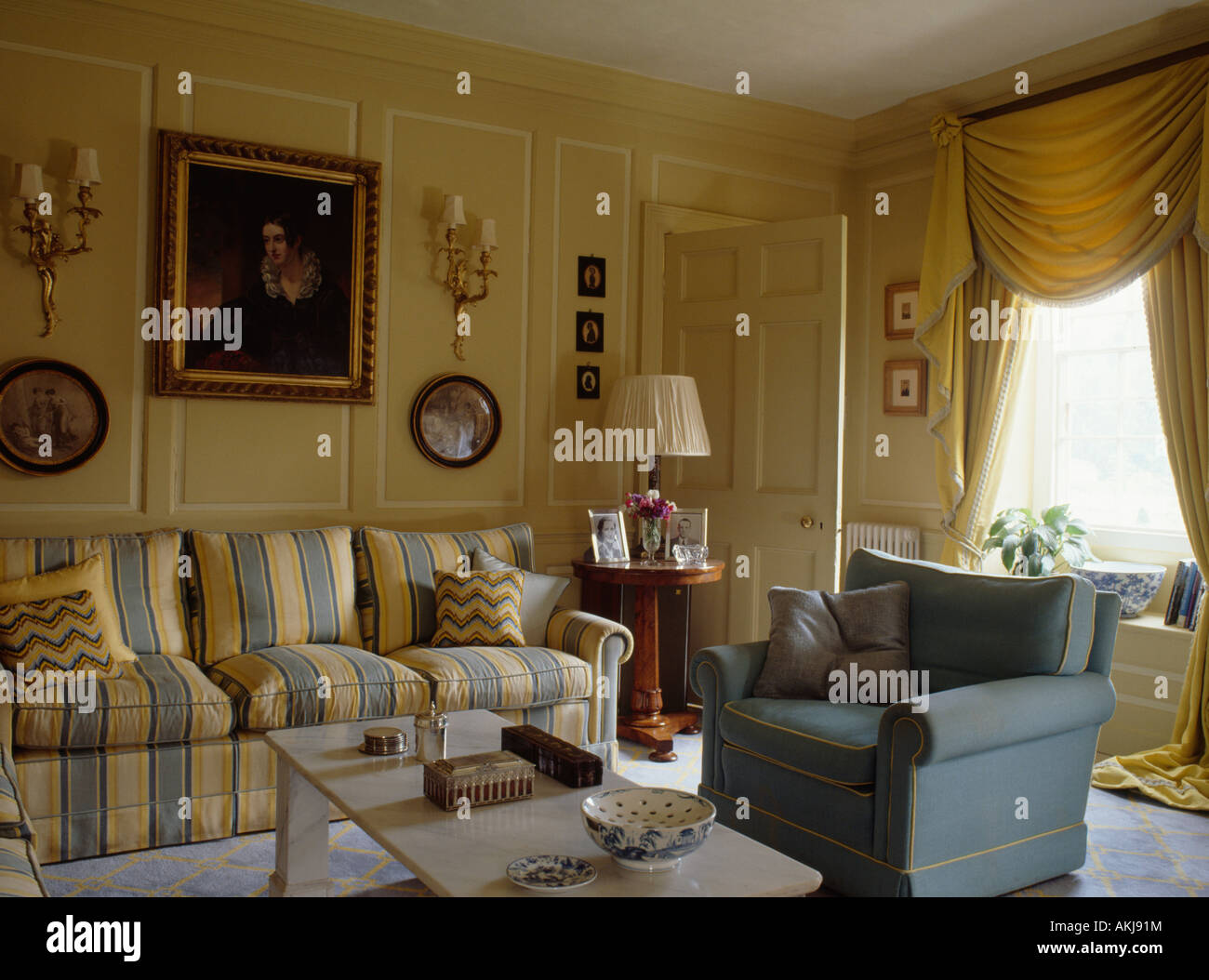 Yellow and blue striped sofa and blue armchair in cream panelled ...