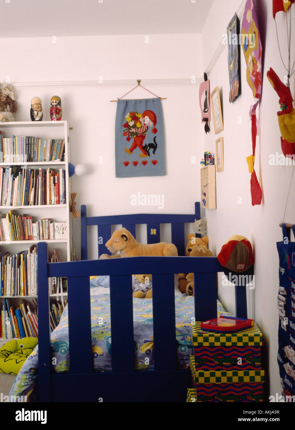 Fabric Wall Hanging Above Blue Wooden Bed In Childs Bedroom With White  Bookshelves