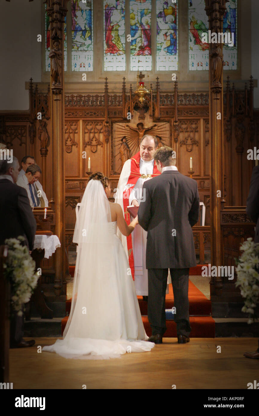 Bride And Groom Stand At The Altar Exchange Vows Rings During A Catholic Wedding Ceremony In Church Cathedral UK