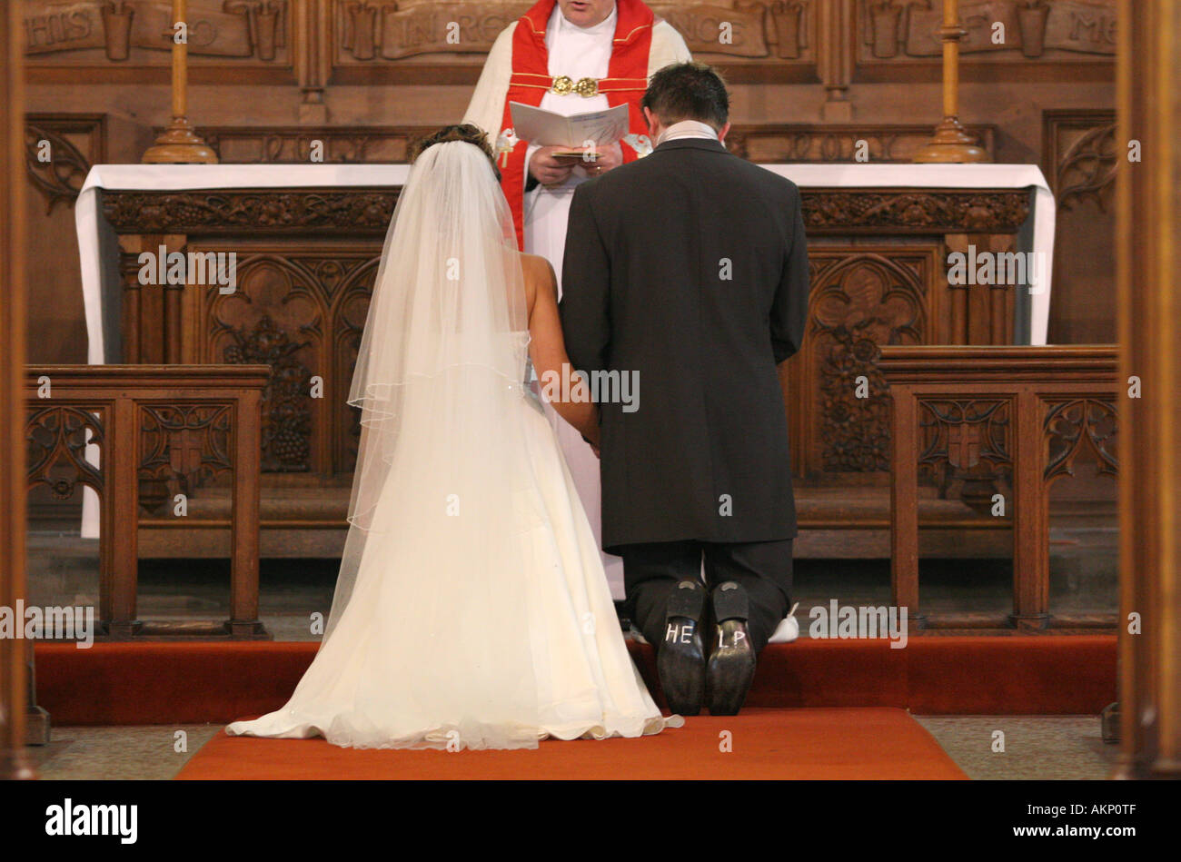groom with help written on soles of shoes kneels at altar during catholic church wedding ceremony uk funny humorous