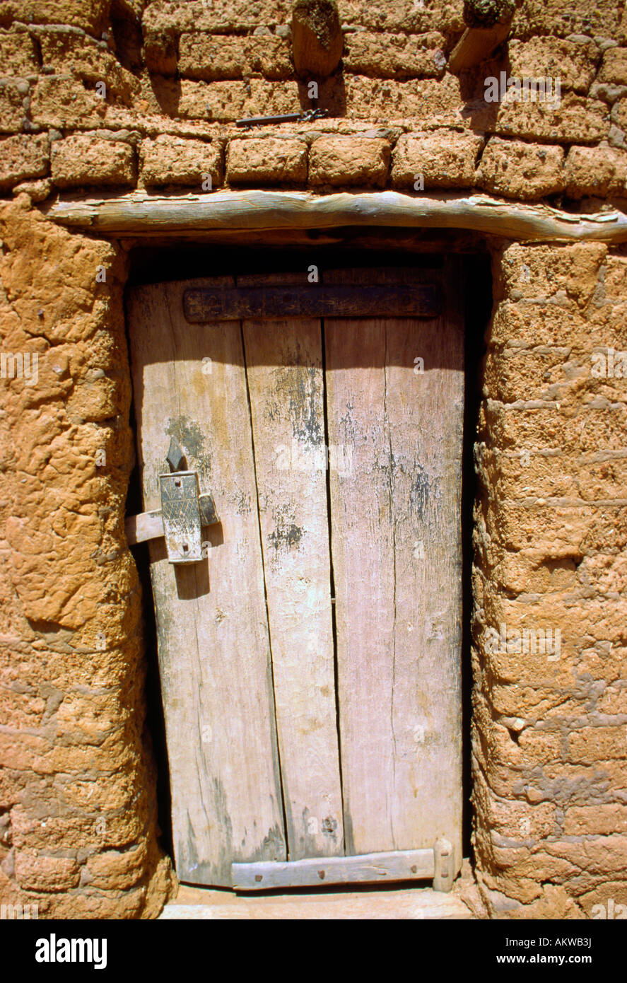A weathered wooden door on a Dogon village house made of clay : clay door - pezcame.com