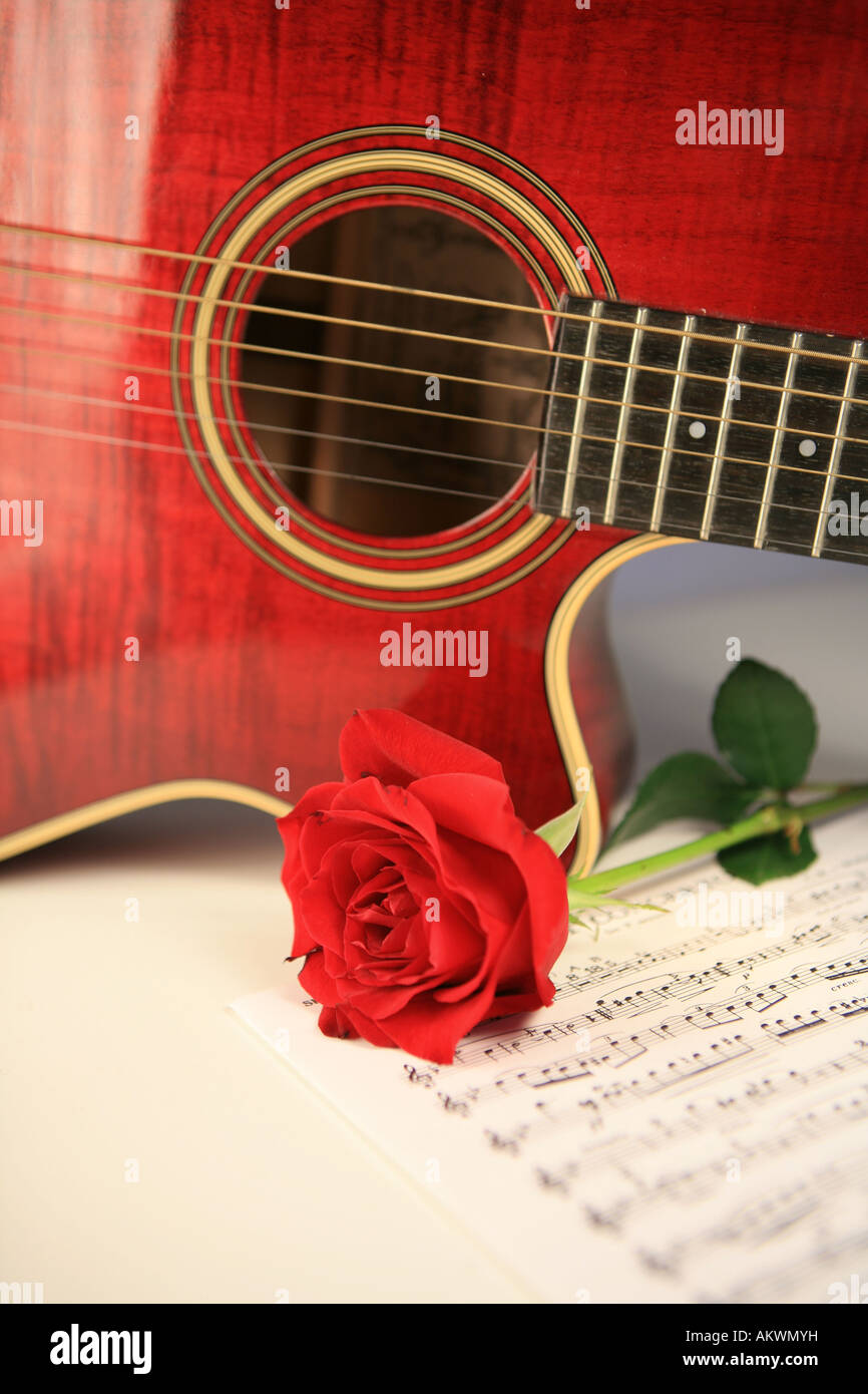 Red Acoustic Guitar With Rose And Sheet Music