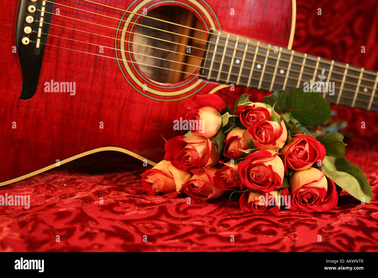 Red Acoustic Guitar With Bouquet Of Roses On Velvet Background