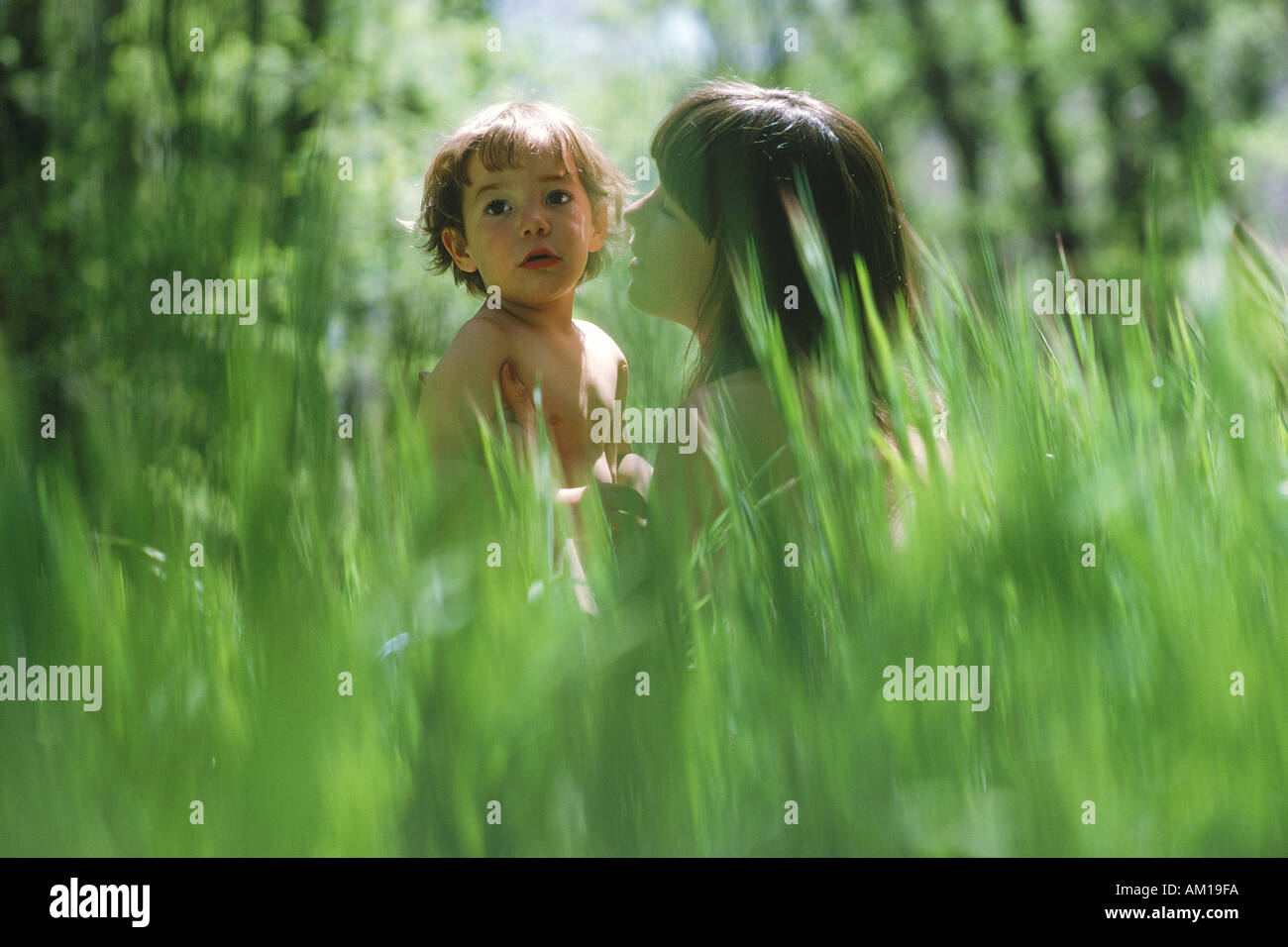 tall green grass field. Mother And Son Sitting In Field Of Tall Green Grass E