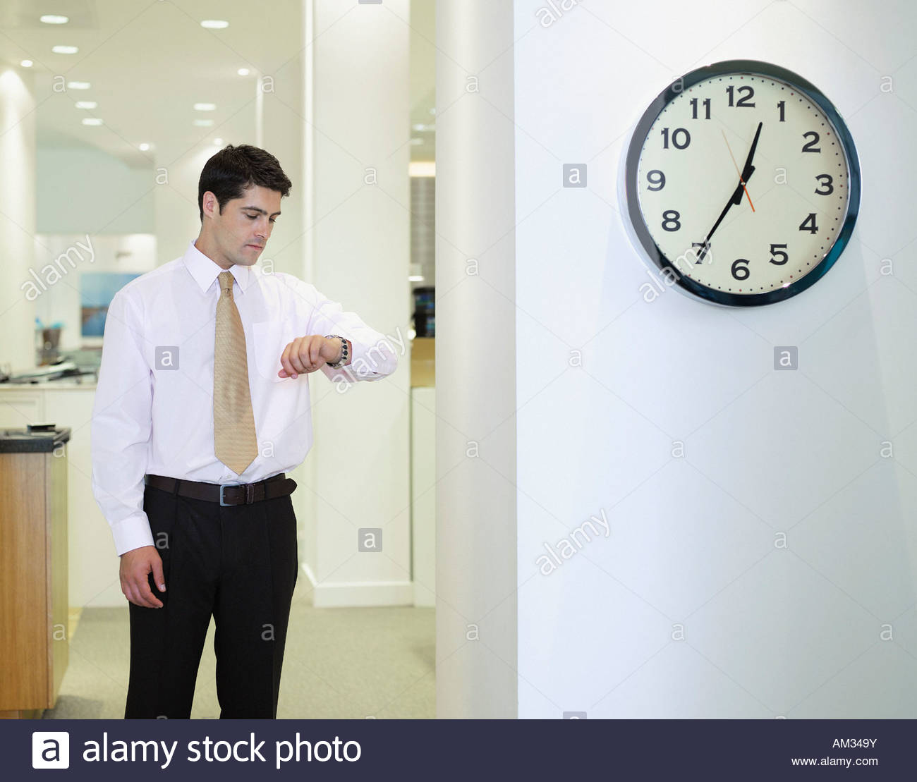 Businessman Checking Watch In Office By Clock Stock Photo