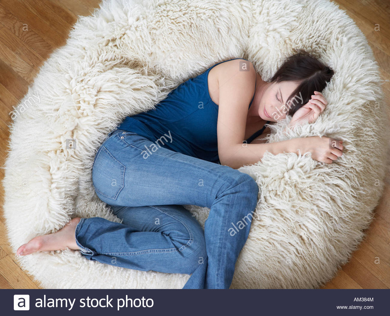 Woman On Furry Bean Bag Chair In Living Room Stock Photo