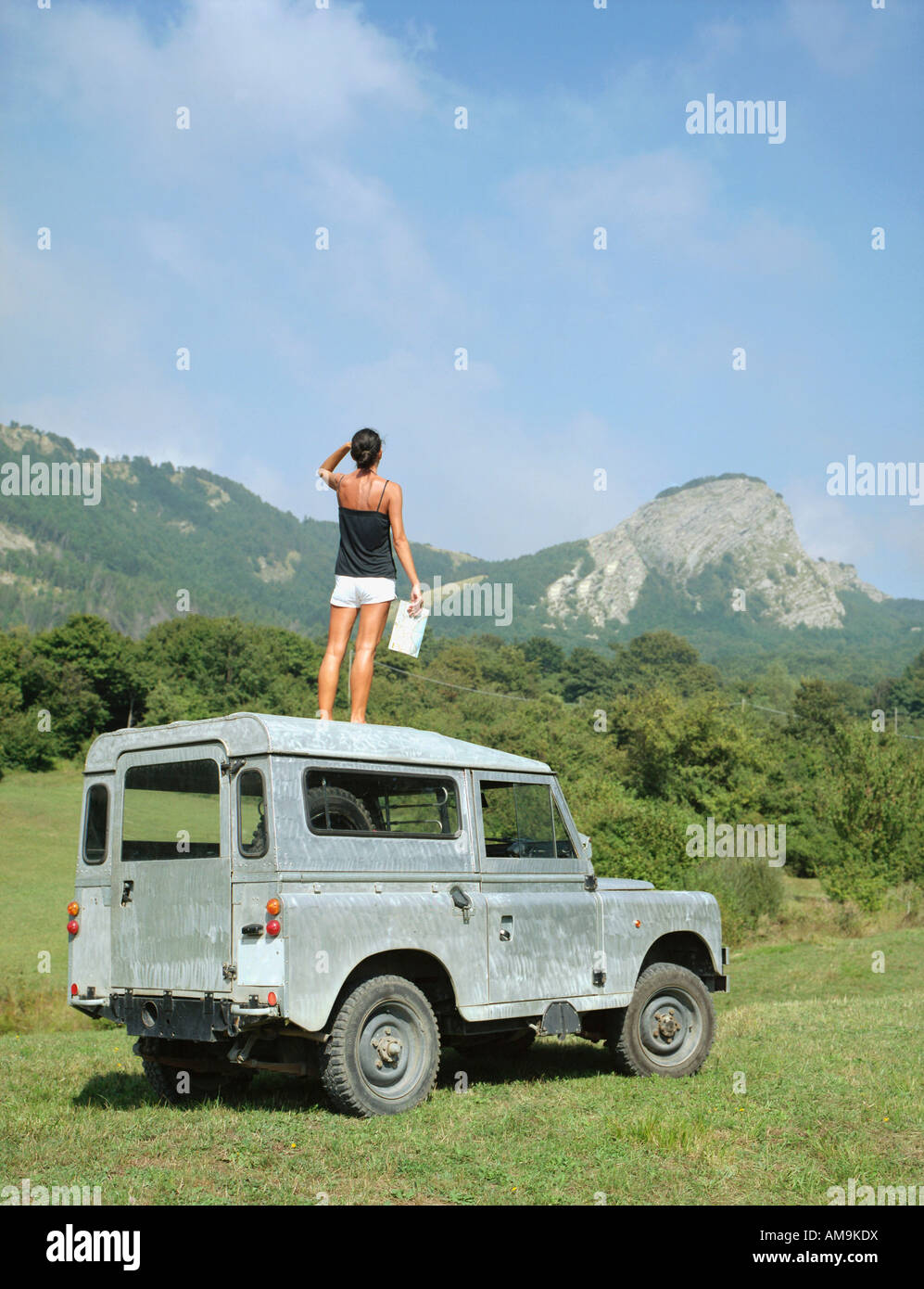 Woman Standing On Roof Of Suv Holding Map Stock Photo Royalty