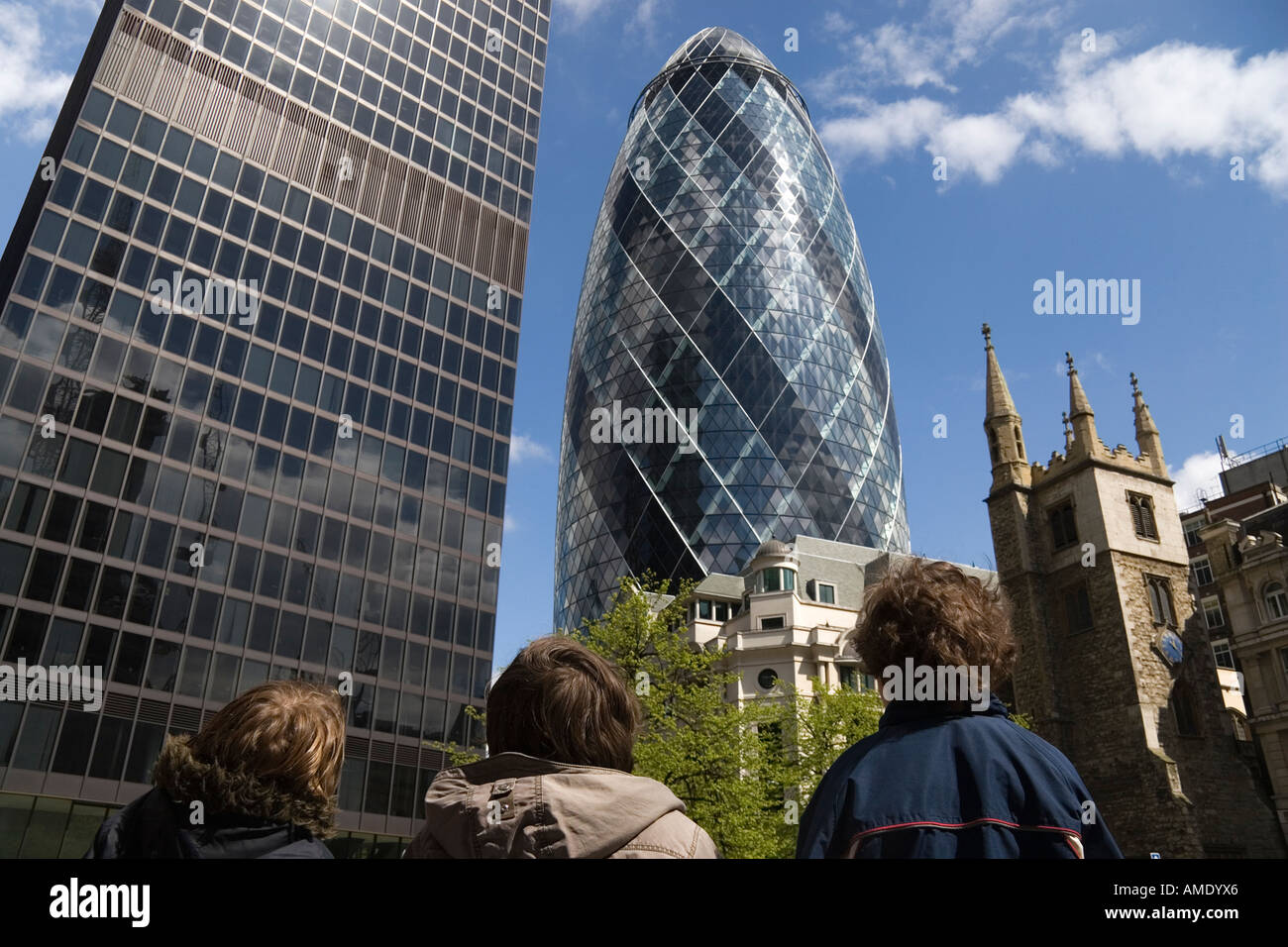 stock photo three boys looking up at the gherkin building in the city of london uk contrasting styles