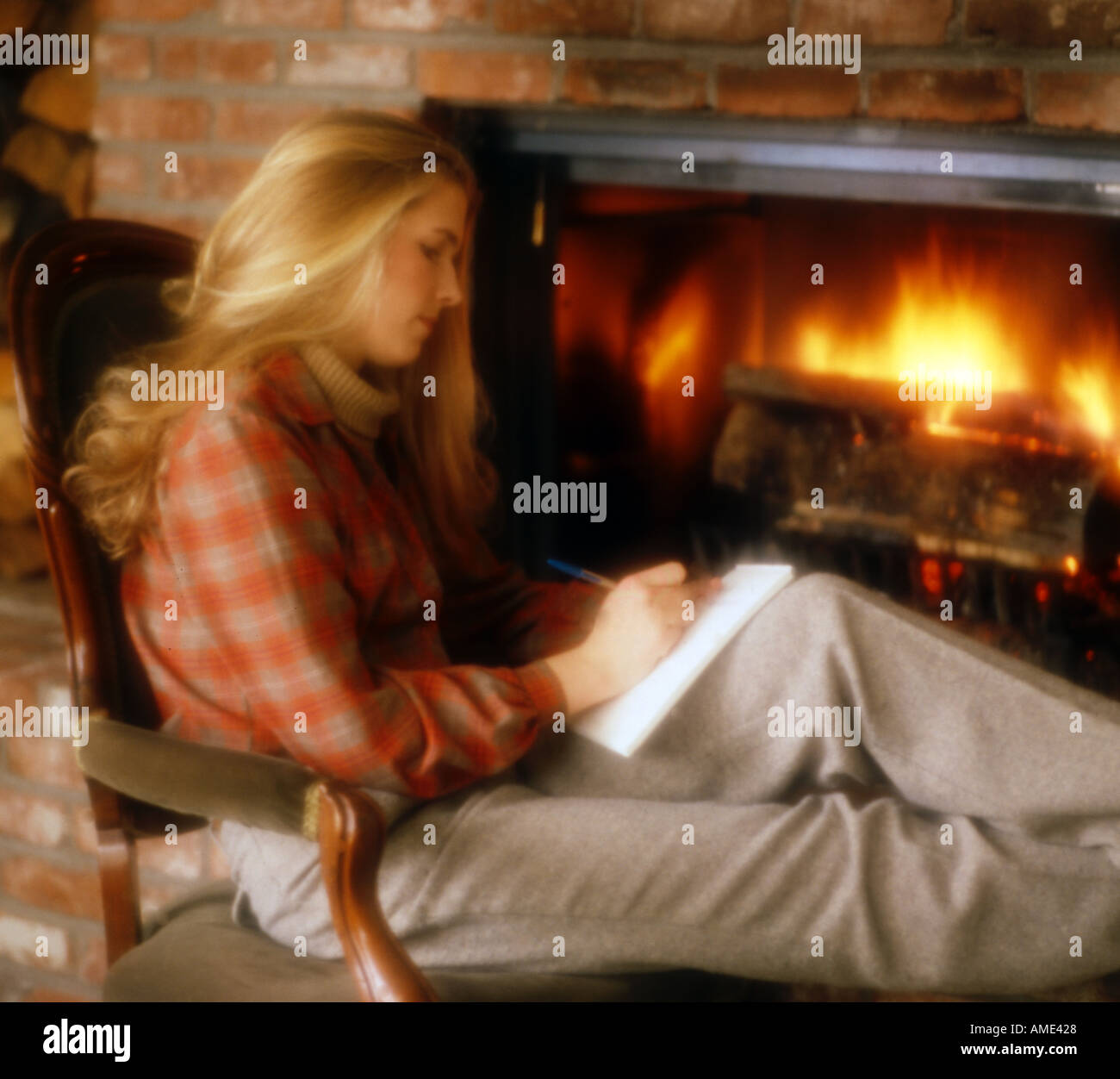 Wistful young woman sitting in front of blazing fireplace Stock ...