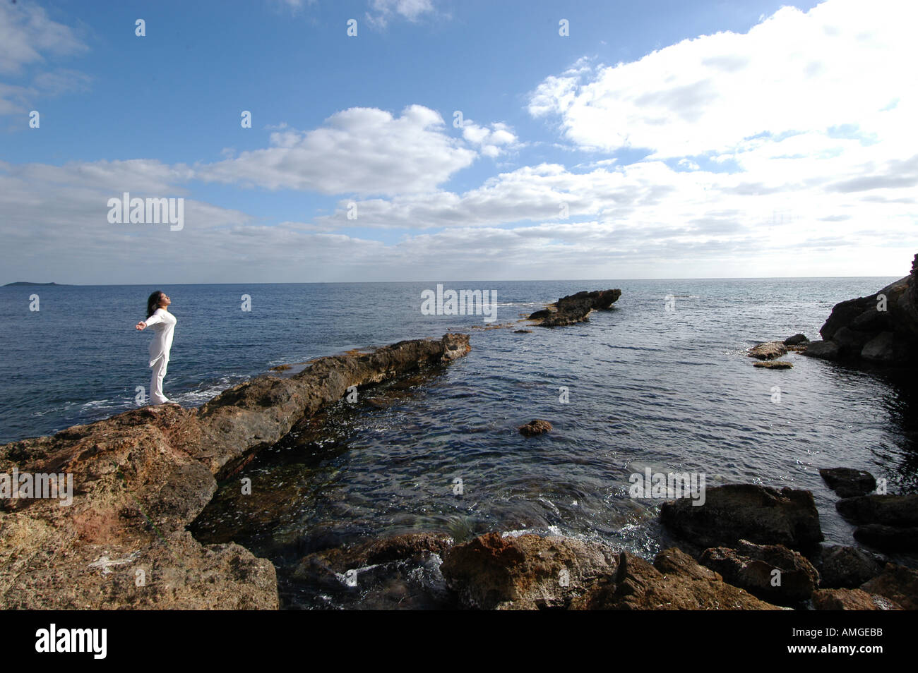 Rocks In Spanish Part - 44: Mixed Race Young Woman Half Asian Half Spanish Standing On The Rocks Next  To The Ocean Breathing And Relaxing In Ibiza Spain