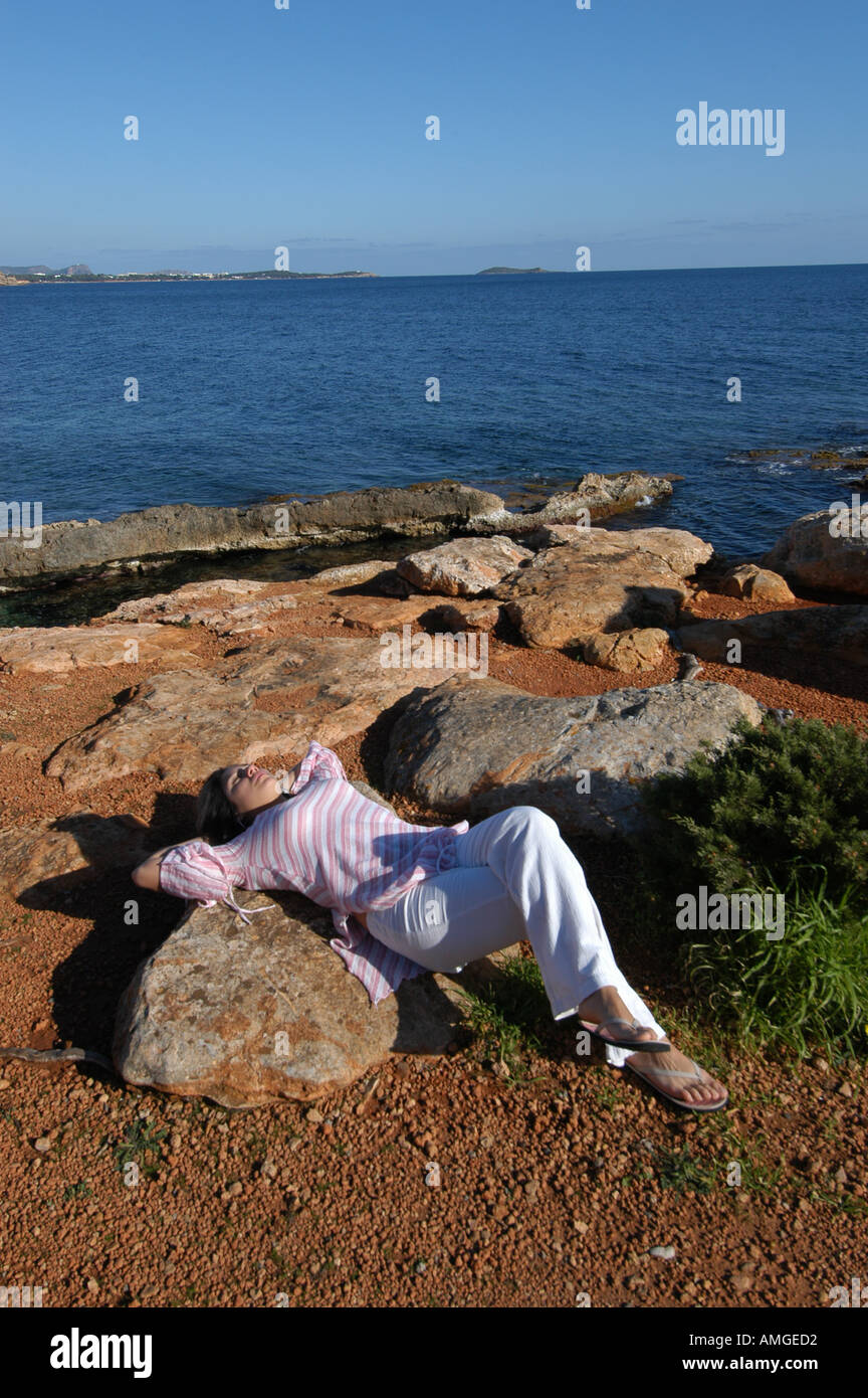 Nice Rocks In Spanish Part - 13: Mixed Race Young Woman Half Asian Half Spanish Laying Down Relaxed On The  Rocks Next To The Ocean In Ibiza Spain