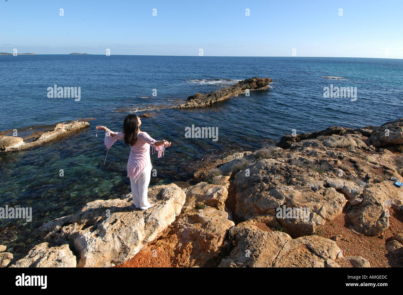 Awesome Rocks In Spanish Part - 12: Mixed Race Young Woman Half Asian Half Spanish Standing On The Rocks Next  To The Ocean Breathing And Relaxing In Ibiza Spain