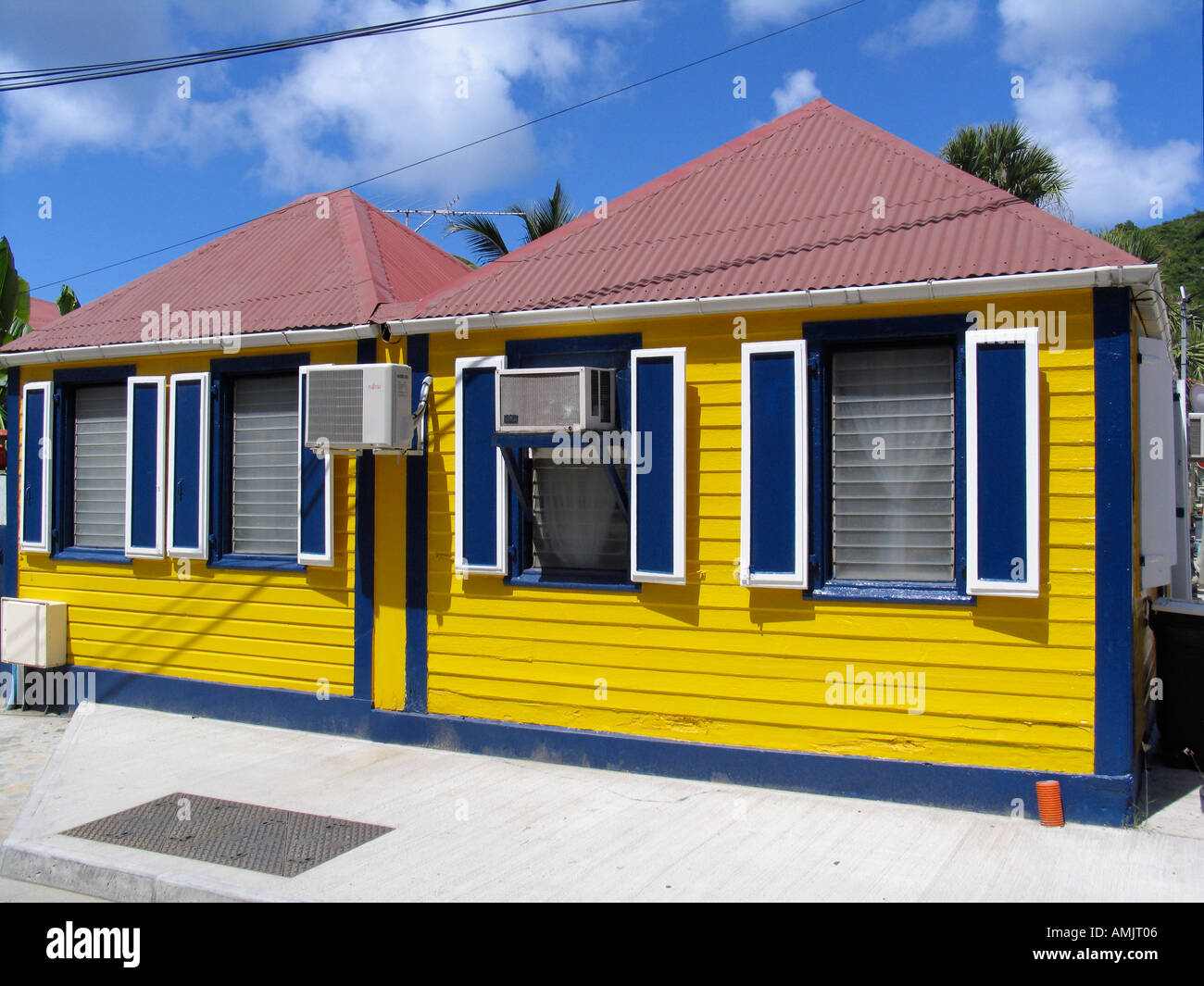 Bright yellow wooden house with red tin roof blue shutters for Modern house yellow