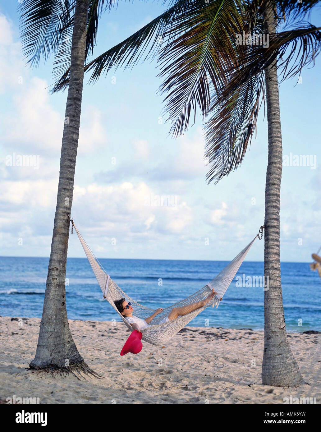 young woman lying in hammock under palm tree on beach phuket thailand   stock woman lying in hammock under palm tree male islands stock photo      rh   alamy