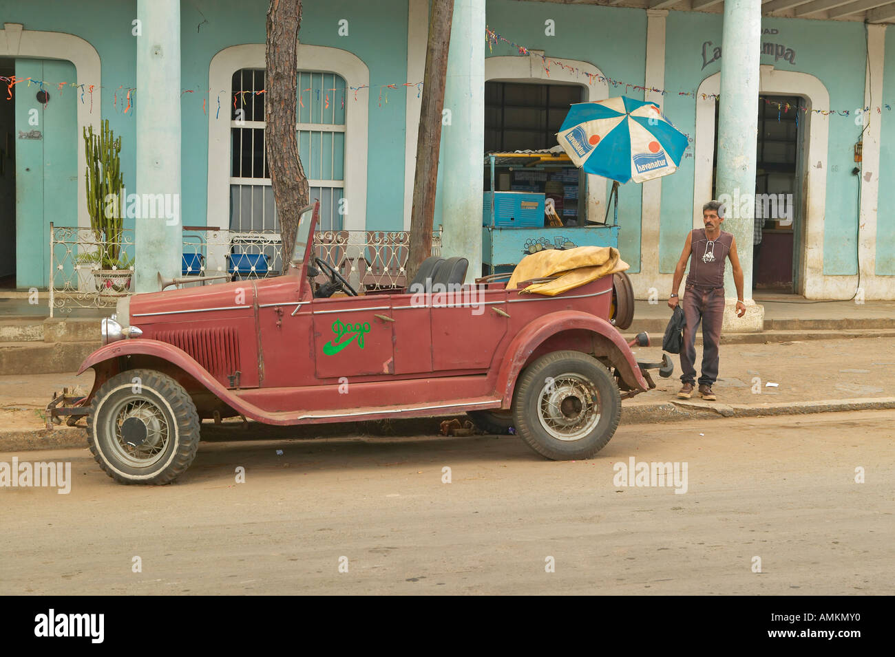 man walking from old stores in rural cuba to old beat up car advertising a restaurant