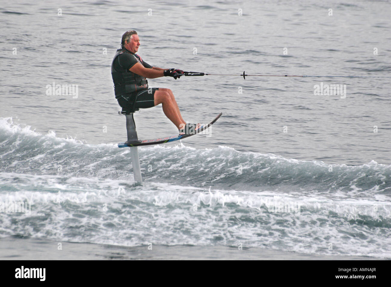Man on water ski chair being pulled at high speed by motor launch – Waterski Chair