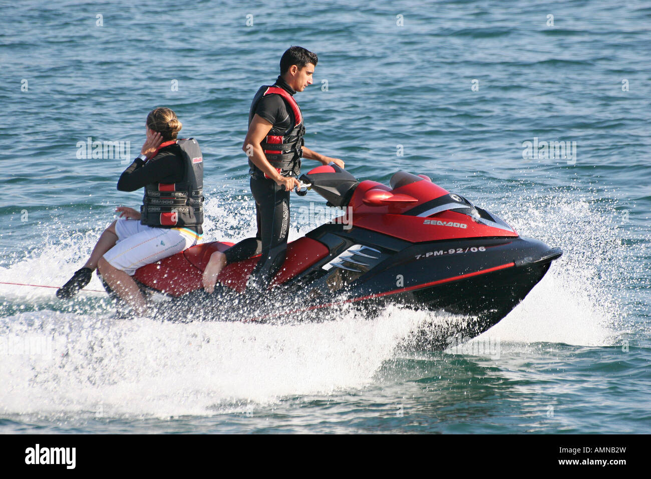 Man And Woman On A Jet Ski Bike With Woman Seated Backwards Stock