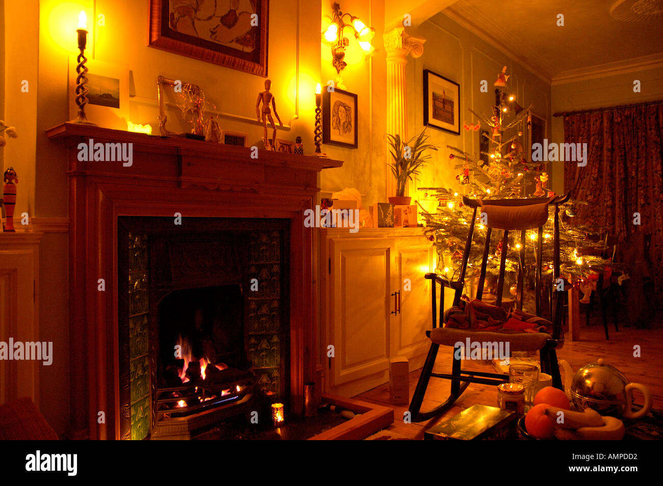 A Rocking Chair By An Open Fire With Christmas Tree And Candles
