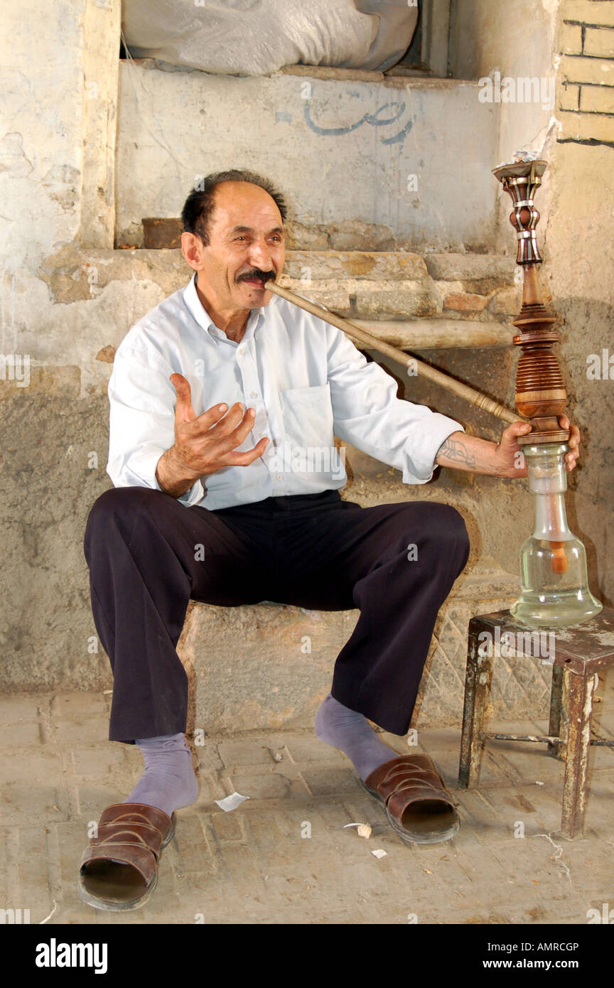 iranian man smoking a hookah pipe in the old bazaar