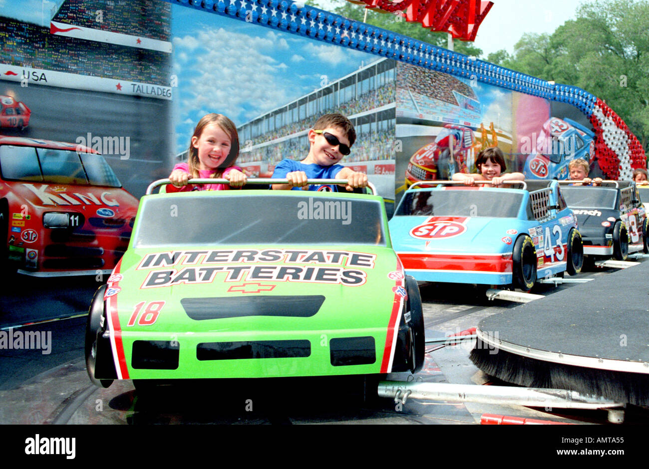 5 year old girl and brother ride race cars at a carnival 2 Stock ...