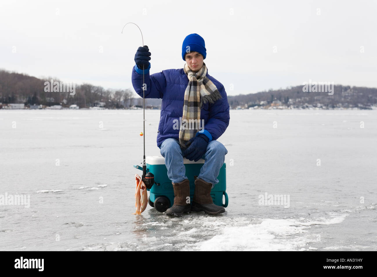 Teenager sitting on a cooler on a frozen lake holding a for Frozen fishing pole