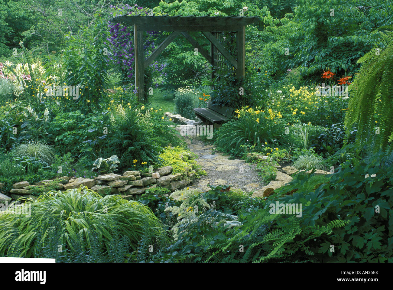 Flagstone Path With Stone Wall In Flower Garden Leads