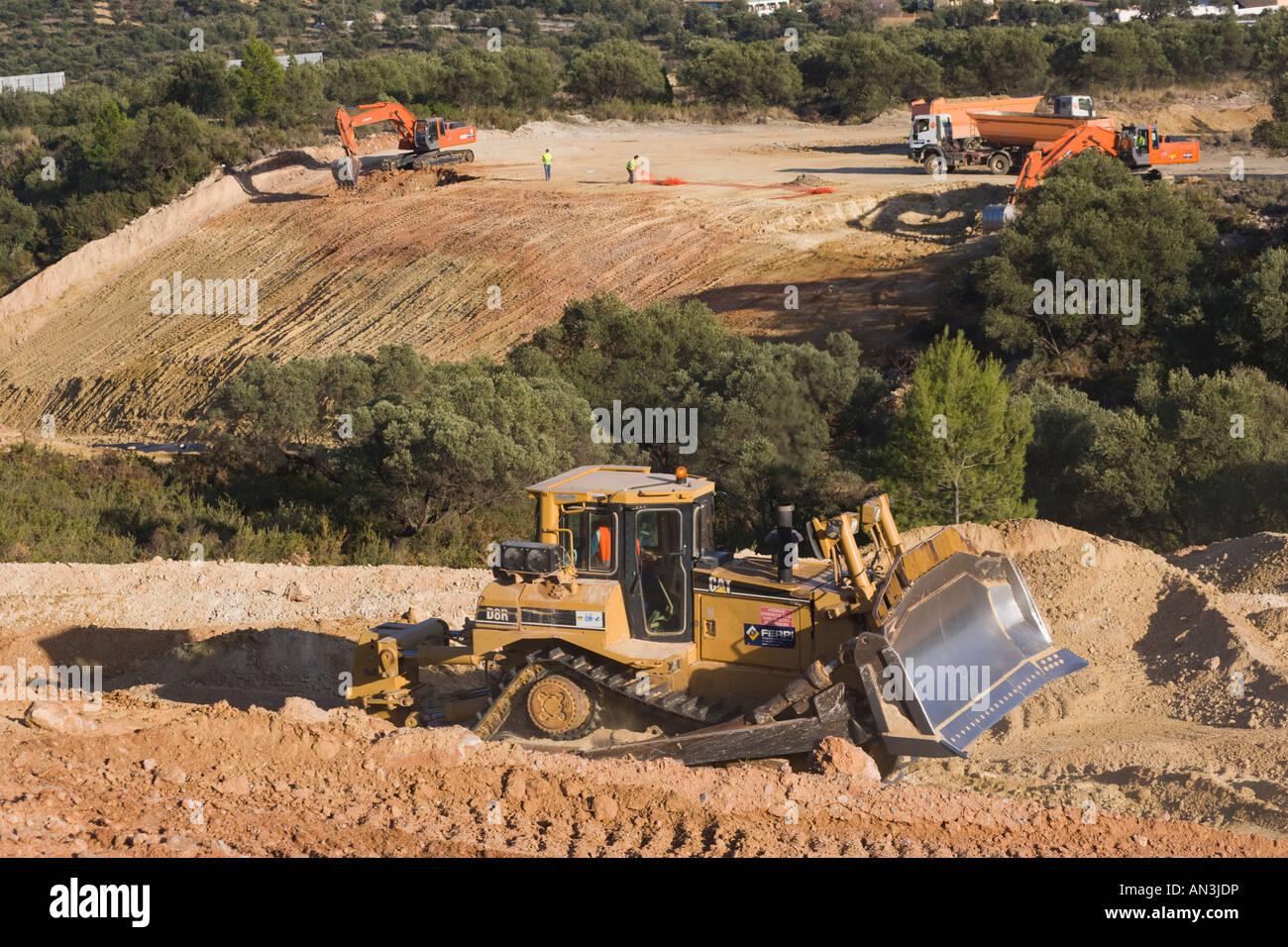 bulldozer mechanical digger and tip trucks at work in spain road