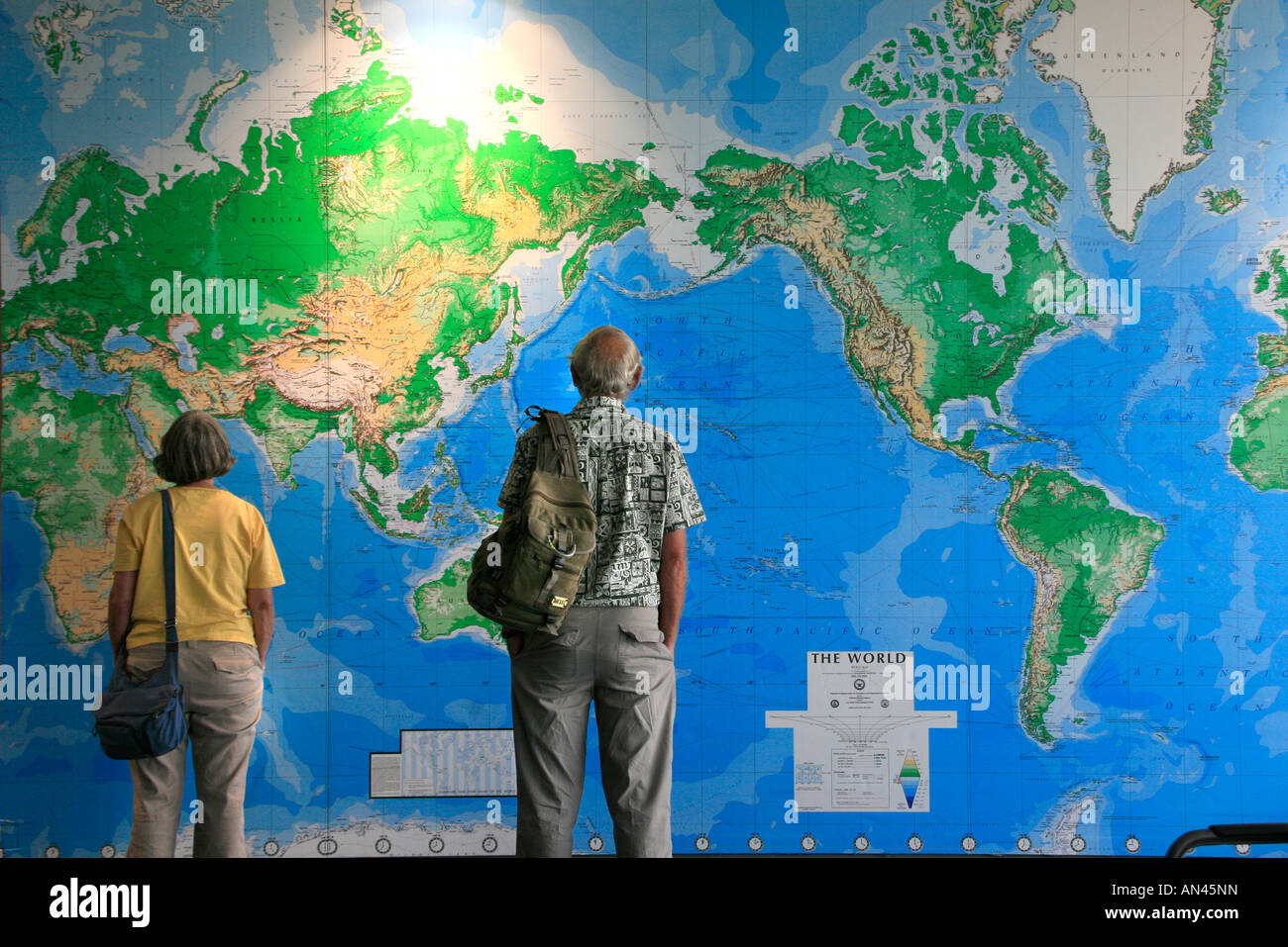 Travelers look at huge wall map of the World in Auckland airport