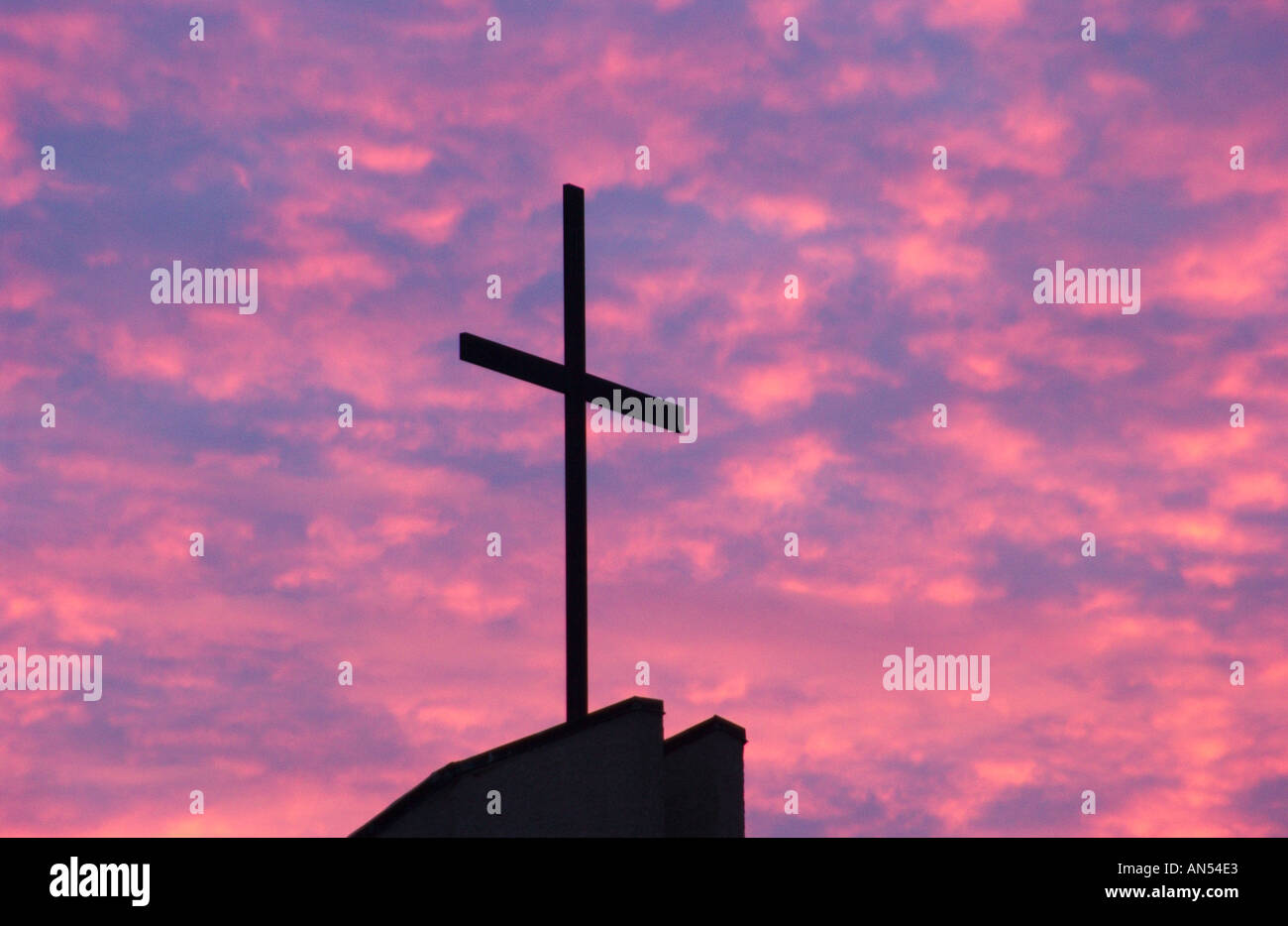 A Cross On Country Church Silhouetted Against Brilliant Sunset Sky