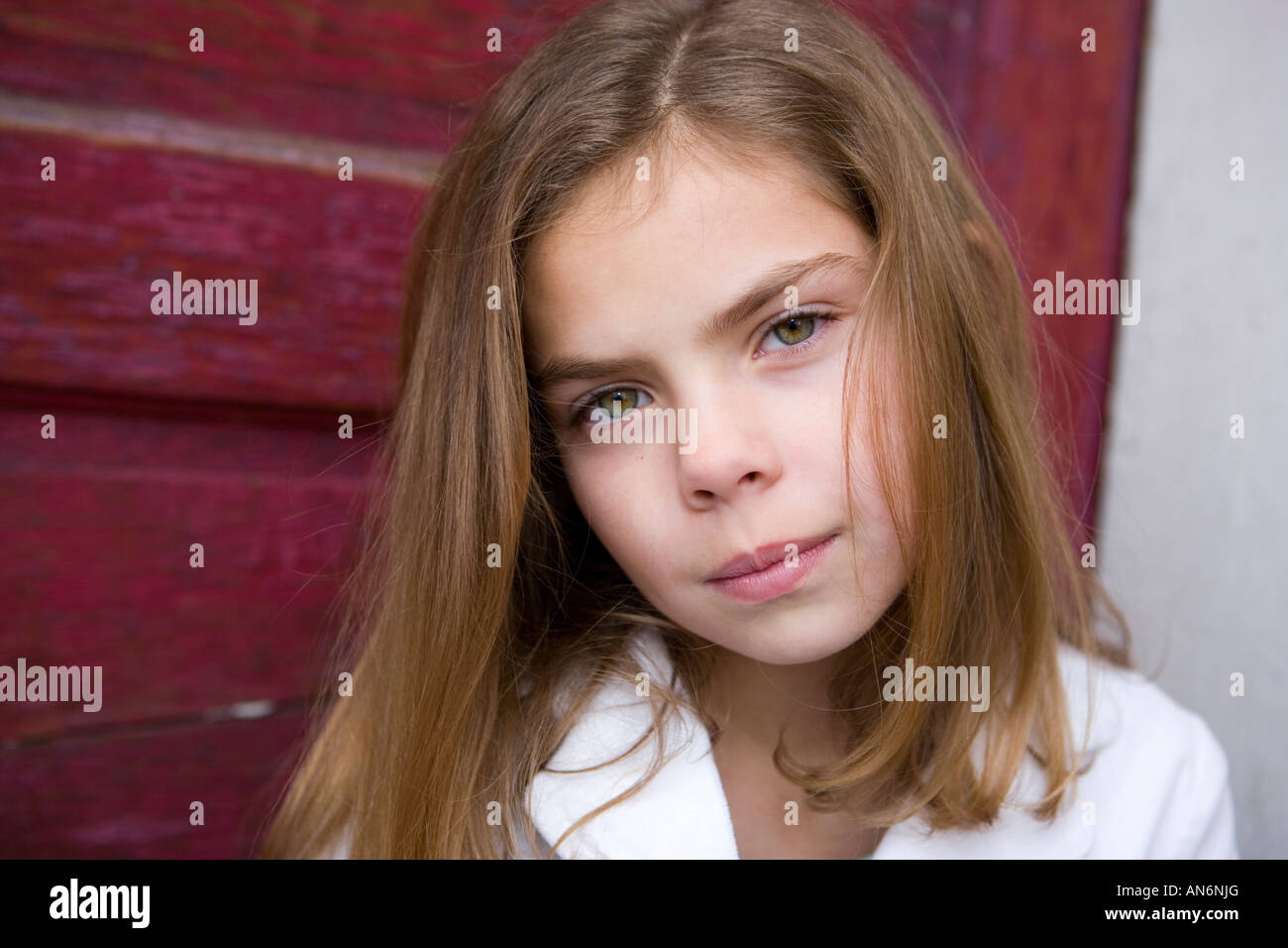 young girl with brown hair and green eyes sitting in front