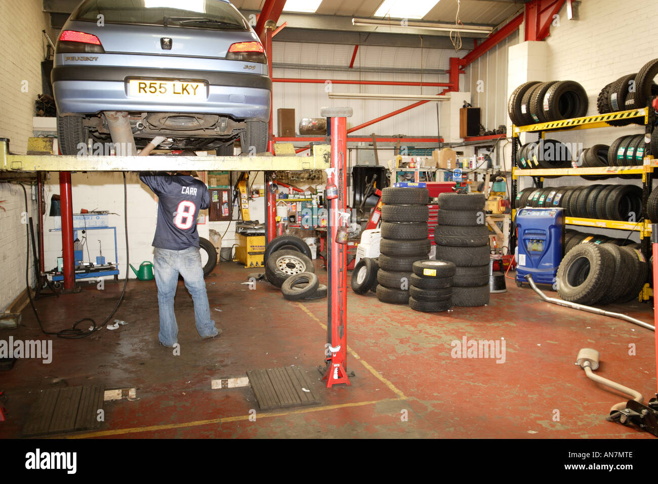 Car Up On Hydraulic Lift At A Garage Mechanic Working