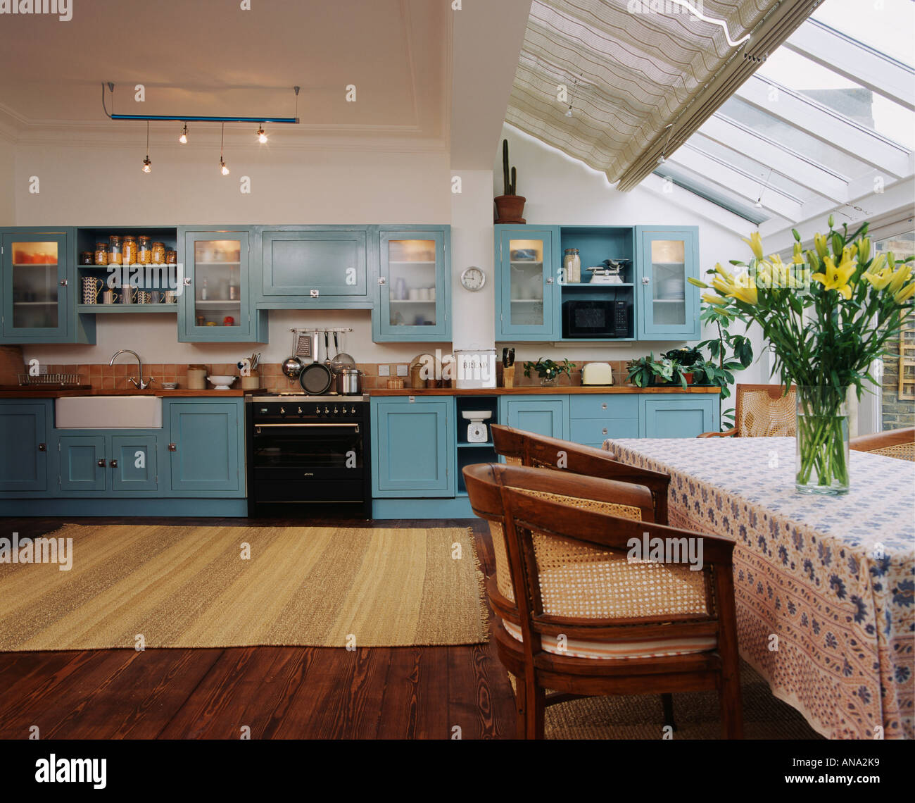 Glass Roof And Wooden Flooring In Spacious Openplan Kitchen Dining Room Extension With Turquoise Fitted Cupboards