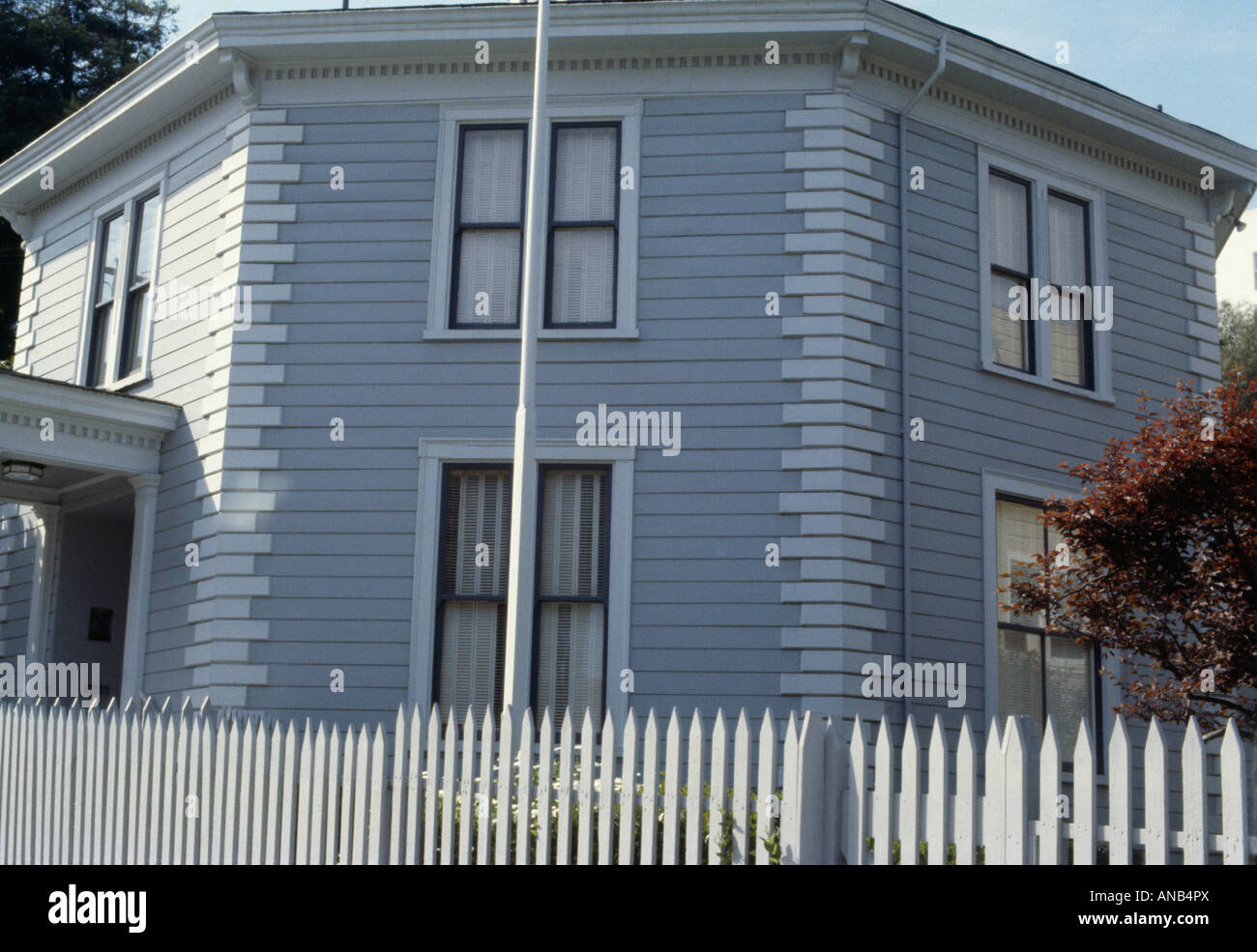 white picket fence in front of grey octagonal house with wooden