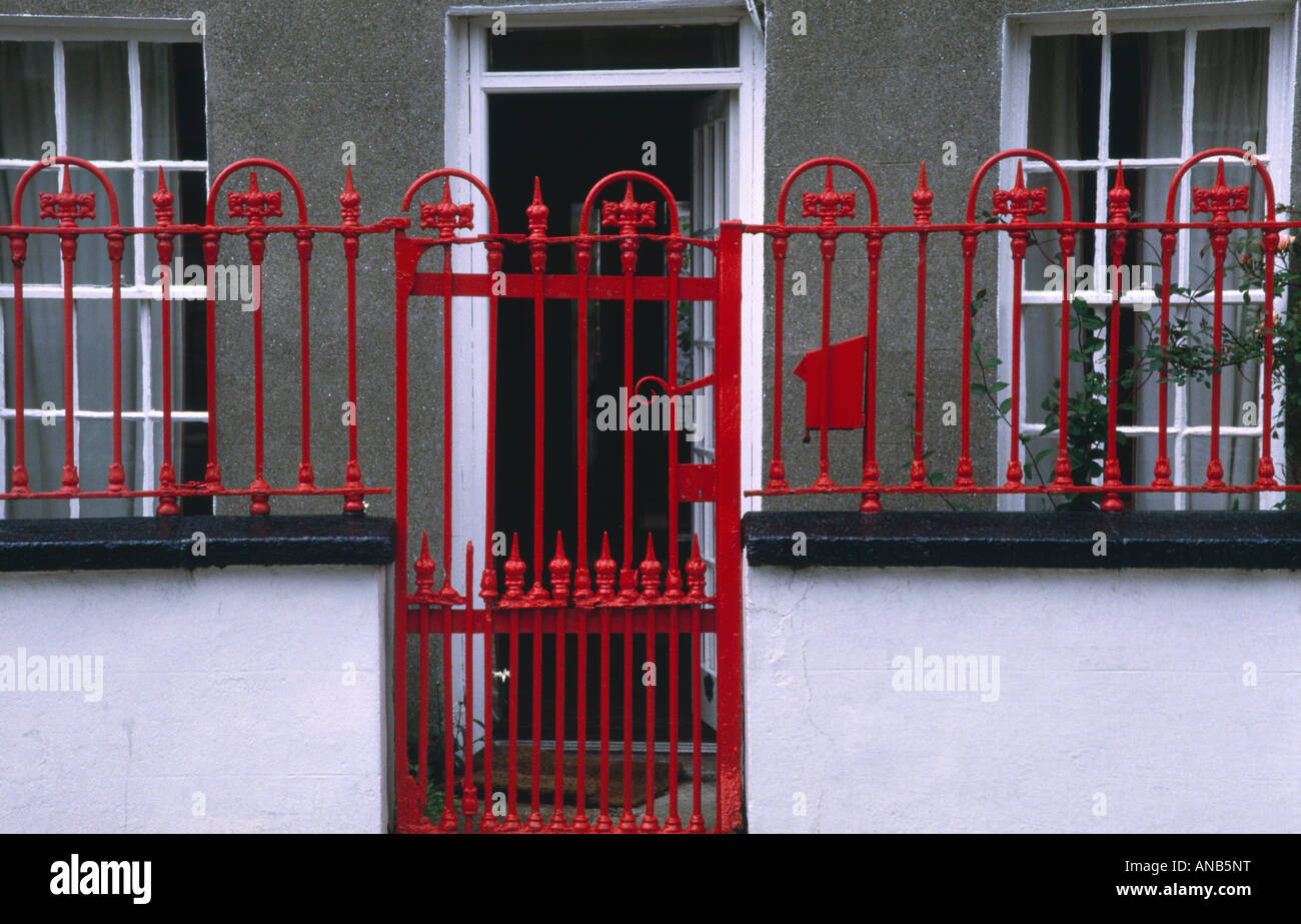 Red Wrought Iron Gate And Fence In Front Of Small
