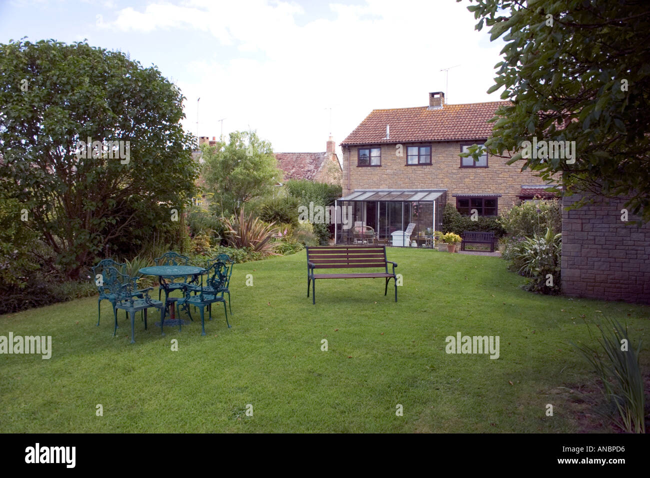 stock photo rear view modern fake hamstone house secluded back garden furniture table bench conservatory rural village tree shrub bush chimn