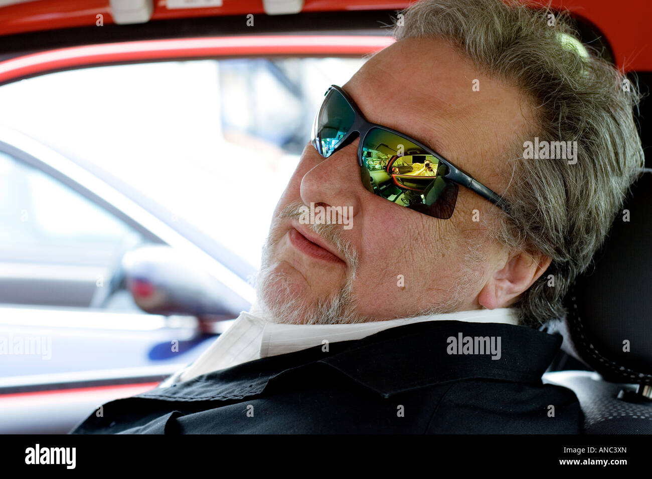 Jet Black, drummer of The Stranglers, sitting in his car ...