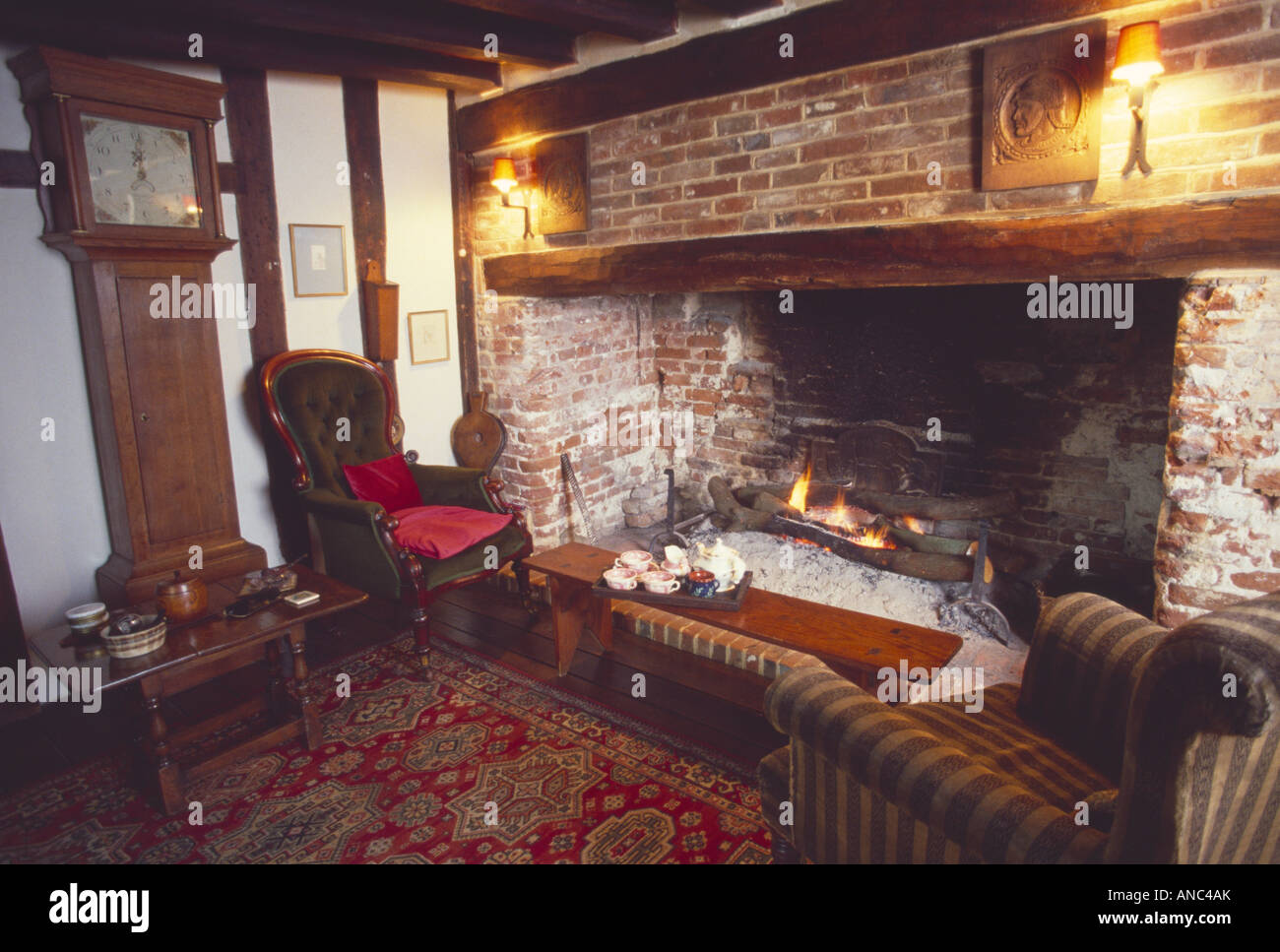 longcase clock and victorian armchair beside inglenook fireplace in seventies cottage living room stock image