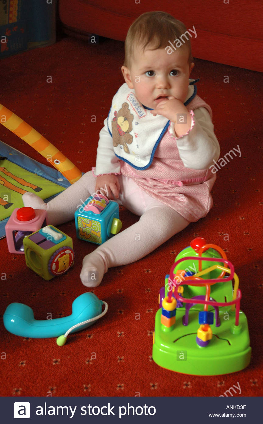 Toys For 9 Month Girl : Month old baby girl sitting up on carpet surrounded by