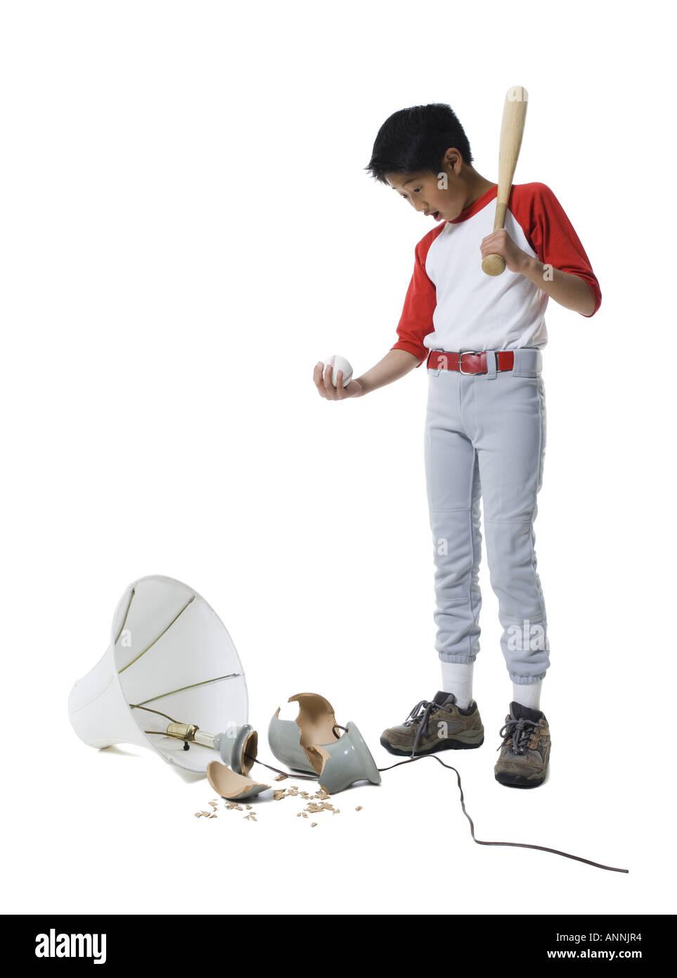 Boy holding a baseball bat with a ball looking down at a broken ...