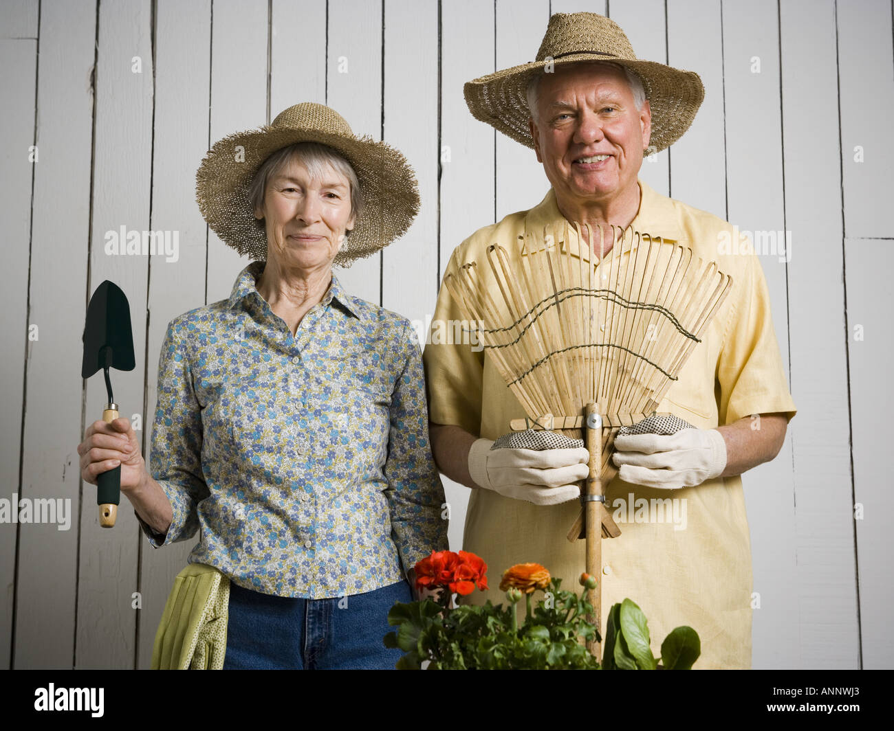 Portrait of an elderly couple standing with gardening tools stock photo royalty free image for Gardening tools for the elderly