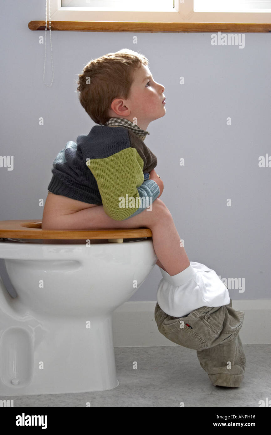 young boy and the toilets Young boy sitting on the loo bog lavatory toilet WC England UK NAOH - Stock Image