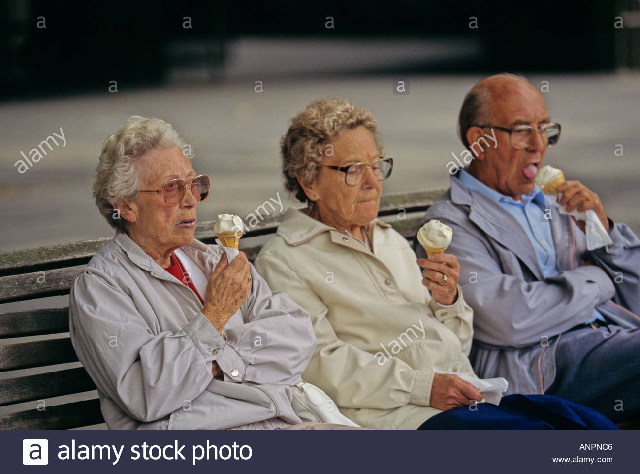Three Elderly People On A Park Bench Eating Ice Creams