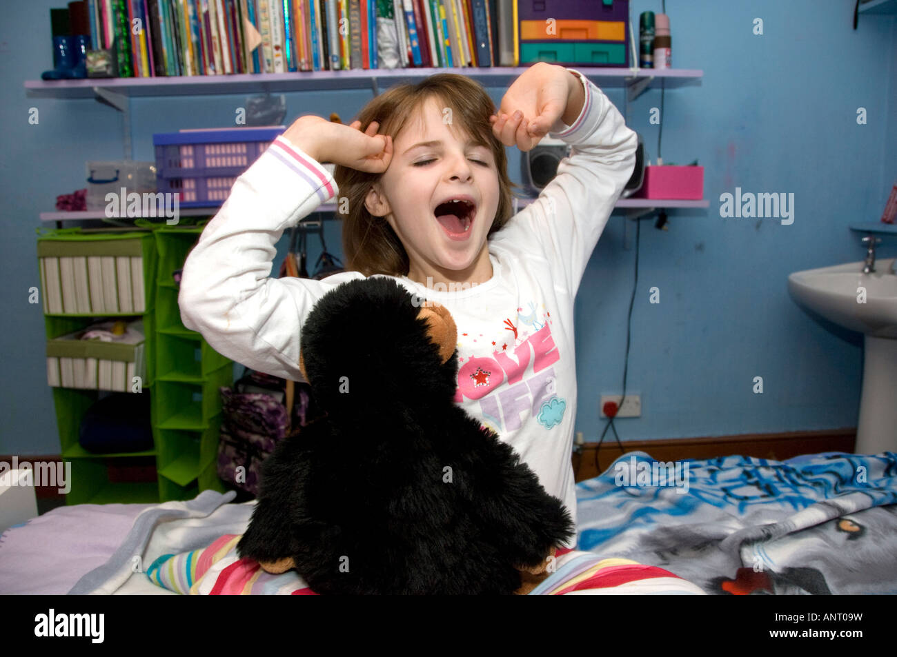 preteen stretch nine year old girl child stretching and yawning, sitting on her bed wearing her pyjamas