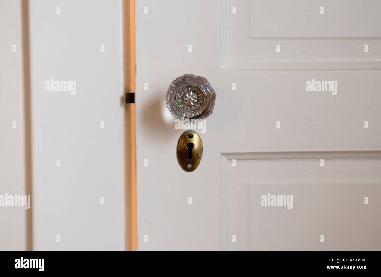Antique glass door knob and brass keyhole on a white wooden door ...
